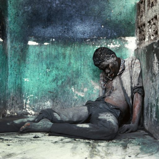The body of a man lays in a small alcove along a well-traveled pathway in Cite Soleil slum in Pt-au-Prince,Haiti. 1987. During weeks leading up to the first democratic elections in 30 years, after the fall of the Duvalier Family dictatorship in Febuary 1986, shooting could be heard throughout the capital and in other cities all night long. In the mornings Haitians would venture out and find bodies of people shot at night by gangs of menopposed to the elections and changes. The murders were meant to scare people from casting their voteson election day in November 1987.