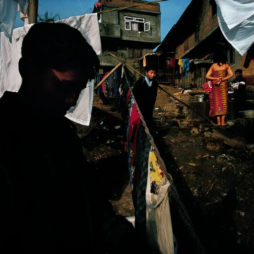 Boy walks through outdoor laundry in a slum near downtown Kathmandu, Nepal. Hand-washed laundry is a big business in the capital because of all the big hotels and people who can afford to have their laundry done, a big business.