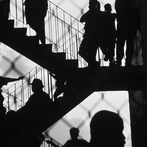 Residents of an apartment building in Liberty City, an African-American neighborhood in Miami, FL., wait outside their apartments on the staircase as police search the area for a gunman.  Miami, FL. 1990.
