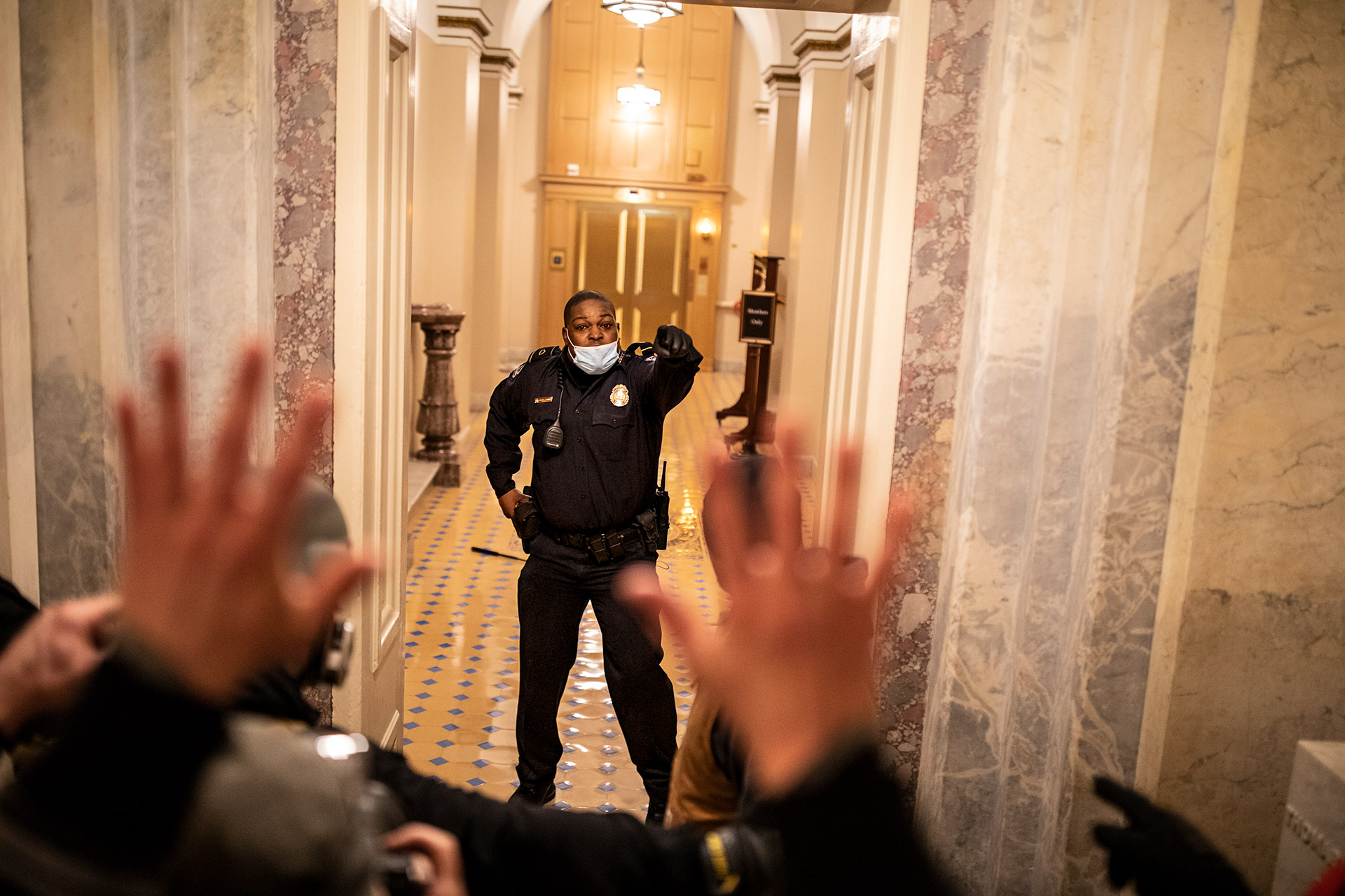 © Ashley Gilbertson / VII for The New York Times Magazine. US Capitol Police (USCP) Officer Eugene Goodman confronts protesters as they storm the Capitol in Washington, D.C. after listening to a speech by President Trump on January 6, 2021