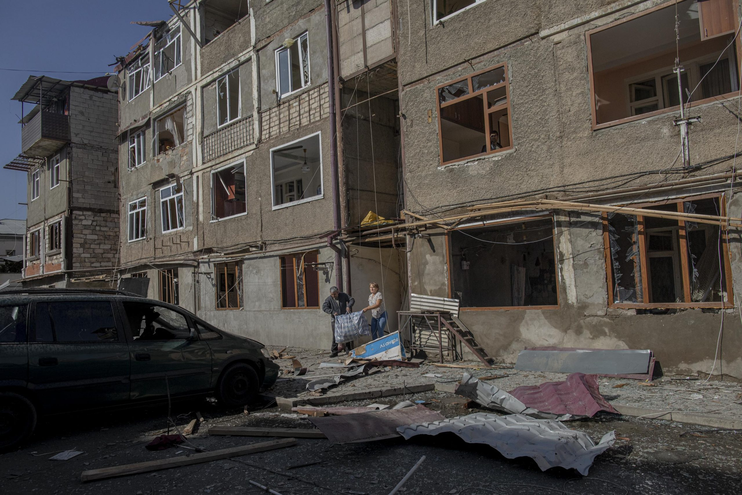 People carry their belongings out of a building damaged by a missile attack, in Stepanakert, Nagorno-Karabakh, on October 3, 2020. The building was damaged on the previous day, October 2.