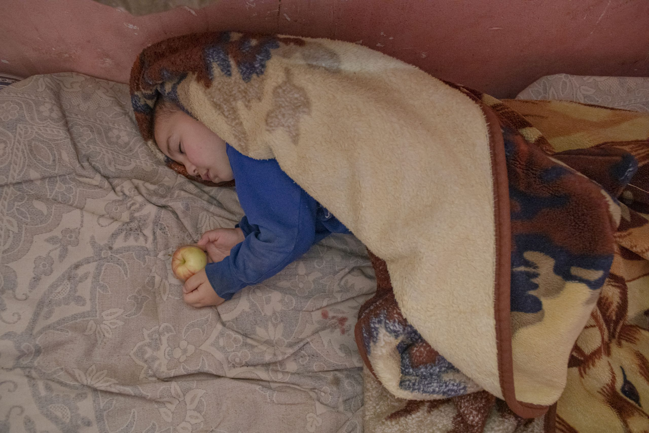 As explosions are heard in Stepanakert and its surrounding area, Movses Babayan, 3, sleeps at his home in Stepanakert, Nagorno-Karabakh, on October 2, 2020. The family has no bomb shelter, they hide under stairs on the first floor, where the child is sleeping.