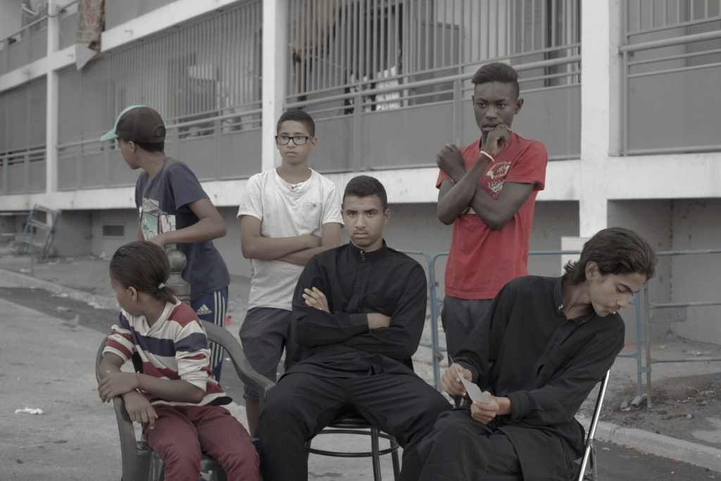 """A group of young men hang out on the streets of their neighborhood Felix Pyat in the northern district of Marseille or """"Quartier Nord"""". The """"Quartier Nord"""" is on the spotlight for being one of the poorest areas of Marseille and by having high crime rates. Marseille, France. Arnau Bach"""