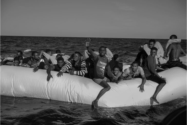 People in distress on a rubber boat just before being rescued at around 20 miles from the Libyan coast with 130 people on board. This Rubber boat left Tripoli the night of 26. An alert was launched by IMRCC ( Italian Maritime Rescue Coordination Centre) of Rome to Aquarius around 4 a.m. The rescue ship of Aquarius get the place around 9 a.m. The rescue operations last 4 hours. At the end of the day 89 people were saved among them 7 children from 15 days to 7 years old. Two women died on board of Aquarius and a third in Sfax in Tunisia where she was transport by an helicopter of Italian navy. 27 January 2018 International water Sicily Channel.